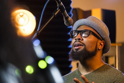 Black man singing in a microphone