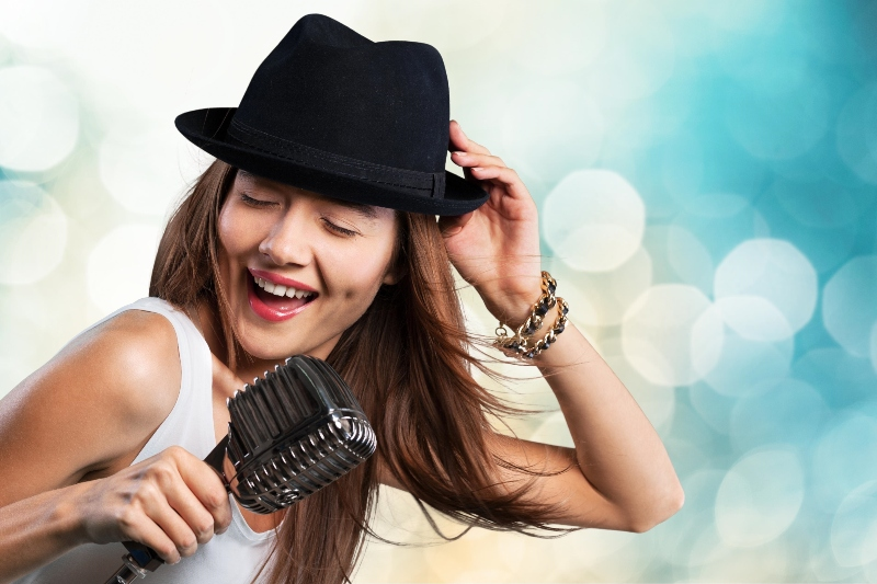 blanke vrouw met hoed en microfoon en zwaaiend haar